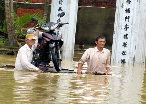 Nước lũ dâng cao, người dân phường Hòa Xuân, Quận Cẩm Lệ, TP Đà Nẵng dùng bè gỗ di chuyển xe máy đến gửi vùng cao an toàn.