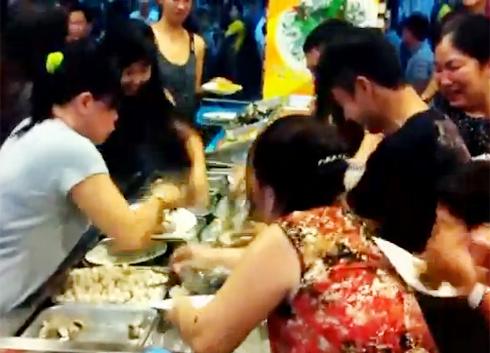 Các thực khách tranh giành thức ăn được cho là trong một nhà hàng buffet ở TP HCM. Ảnh cắt từ clip.