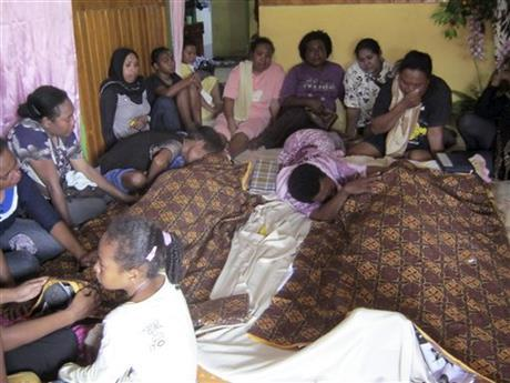 Relatives mourn around the bodies of Yanus Manibui and his wife Anance Woyaa who were victims in a stampede at Kota Lama Sport Stadium after spectators rioted to protest a local boxer's loss in Nabire, Papua province, Indonesia, Monday, July 15, 2013.