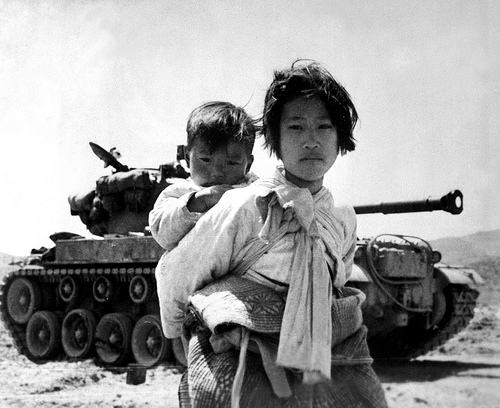 With her brother on her back a war weary Korean girl tiredly trudges by a stalled tank, at Haengju, Korea. June 9, 1951. Maj. R.V. Spencer, UAF. (Navy) NARA FILE #: 080-G-429691 WAR & CONFLICT BOOK #: 1485  Cleared for public release. This image is generally considered in the public domain - Not for commercial use.  U.S. Army Korea - Installation Management Command