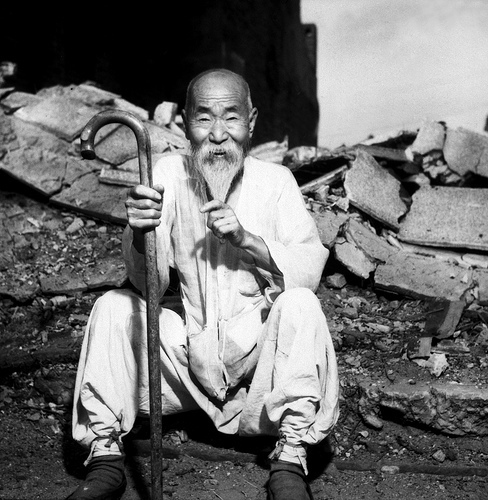 An old Korean man takes a rest on the street in front of destroyed buildings, in Seoul. August 20, 1951. G. Dimitri Boria. (Army)