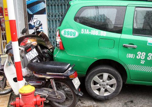 3 xe máy bị taxi ép kẹt phía sau. Ảnh: An Nhơn