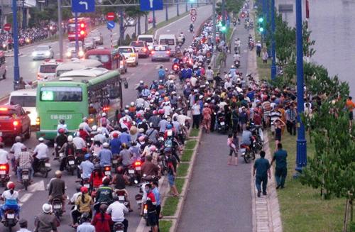 Đoạn đường bị ùn tắc vì hàng trăm người đứng xem cảnh sát tìm thi thể nam thanh niên nhảy cầu tự tử. Ảnh: Châu Thành