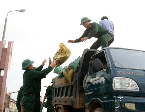 Ban chỉ huy quân sư huyện Lộc Hà huy động hơn 40 chiến sĩ để lấy bao tải cát che chắn lên mái tôn của trường Mầm non xã Thạch Kim. Ảnh 2: Công an, lực lượng thanh niên xung kích cũng giúp dân dùng bao cát đè lên mái tôn.