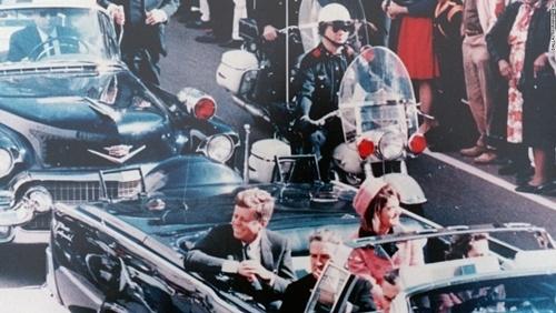 Tổng thống Kennedy (trái) và vợ Jacqueline Kennedy vẫy chào người dân Texas ngay trước khi bị bắn.
