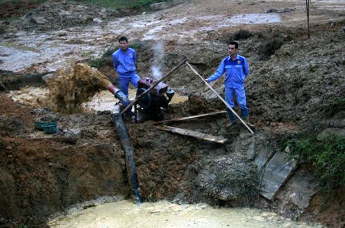 Các công nhân đang bơm nước để tiếp cận đường ống bị vỡ, sâu dưới lòng đất khoảng 5m. Ảnh: Bá Đô