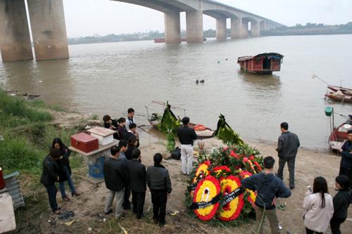 Sau đám tang diễn ra chiều nay tại nhà tang lễ Thanh Nhàn, gia đình chị Huyền chuyển vòng hoa và bát hương ra sông Hồng, lập mộ gió cho chị. Ảnh: Phương Sơn