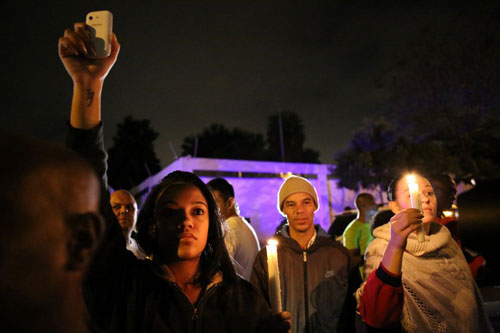 [Caption] South Africans hold a candlelight vigil outside the house of former South African president Nelson Mandela following his death in Johannesburg on December 5, 2013.