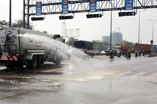 Nhân viên tưới công viên phun nước rửa hóa chất trên đường. Ảnh: An Nhơn