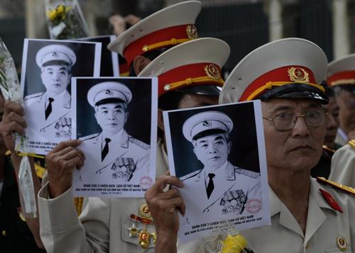 Các cựu chiến binh giơ cao ảnh người anh cả của Quân đội Nhân dân Việt Nam trước khi vào viếng Đại tướng sáng 10/10.  AFP