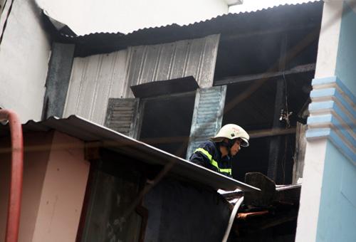 Cảnh sát leo lên mái tôn để phun nước dập lửa ở căn gác. Ảnh: An Nhơn