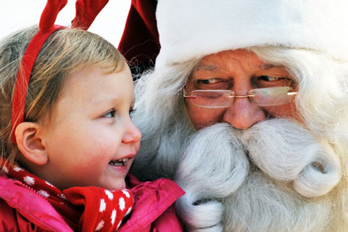 [Caption]A man dressed as Santa Claus from Lapland, Finland listens to a girl's Christmas wish on stage at a Christmas event organised by the Finnish embassy in Seoul on December 23, 2013. Christmas Day is a holiday in South Korea, as the country has East Asia's largest Christian community after the Philippines, with about 8.6 million Protestants and 5.1 million Catholics.