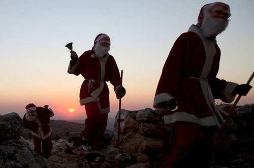 [Caption]Palestinian men dressed as Santa Claus walk around the mixed Christian and Muslim village of Abud, close to the West Bank city of Ramallah, on December 22, 2013, two days ahead of Christmas celebrations