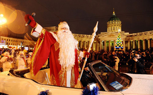 [Caption] A man dressed as 'Father Frost' waves from a car in front of the Kazansky Cathidral during a festival parade in central St. Petersburg on December 22, 2013. St. Petersburg is preparing for New Year festivities and the Orthodox Christmas which Russians celebrate on January 7