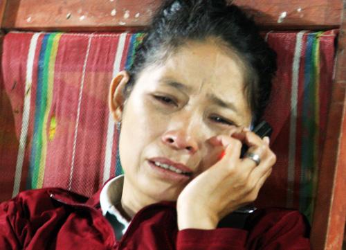 Bà Loan vừa khóc vừa trả lời điện thoại cho người thân ở quê về thông tin cậu con trai mất tích. Ảnh: An Nhơn