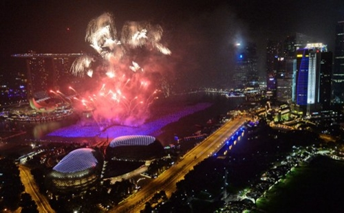 Pháo hoa rực sáng trên bầu trời Singapore.Fireworks burst over the Singapore skyline during New Year celebrations on January 1, 2014. An eight-minute firework display was launched in a five-pronged formation that illuminate the skyline to welcome 2014.