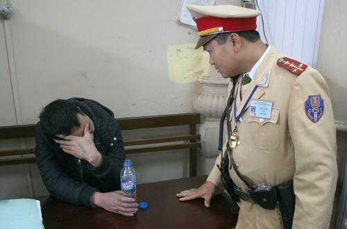 Đại úy Trần Phong đang tra hỏi tên cướp tại trụ sở công an. Ảnh: Bá Đô