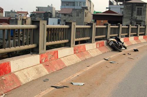 Chiếc xe máy bị biến dạng sau cú va chạm vào thành cầu. Nhiều mảnh vỡ bắn tung tóe. Ảnh: Phương Sơn