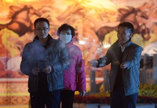 Một gia đình đốt pháo sáng trong đêm giao thừa tại một quảng trường ở thành phố Lan Châu, thủ phủ tỉnh Cam Túc, Trung Quốc. Ảnh: AFP.