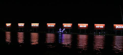 Dòng chữ khổng lồ về đêm nhìn từ bên bờ quận 1. Ảnh: An Nhơn