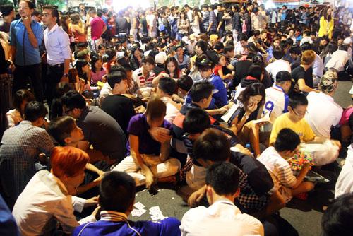 Tối 30/1, hàng chục nghìn người đổ nhau về trung tâm TP HCM để xem bắn pháo hoa. Trong lúc chờ đợi, mọi người mua đồ ăn, lót giấy ngồi và vô tư vứt bừa bãi trên thảm cỏ, dưới đường.