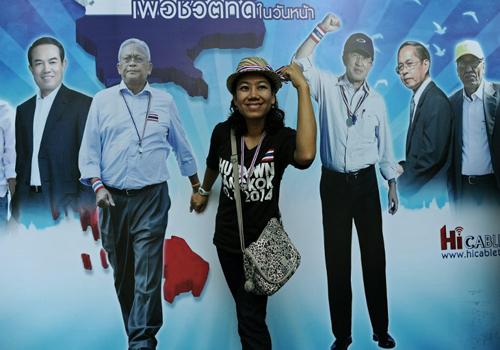 Một người tạo dáng trước tấm panô có hình ảnh của thủ lĩnh biểu tìnhSuthep Thaugsuban (thứ hai từ trái sang) tại một điểm biểu tình ở Bangkok hôm qua. Ảnh: AFP