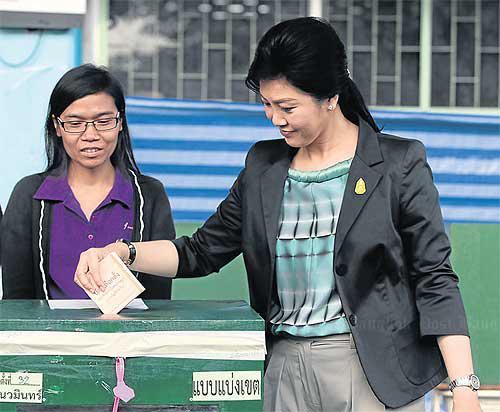 [Caption]Bà Yingluck bỏ nhầm phiếu da cam vào hòm theo đơn vị bầu cử, trong khi đáng lẽ nó phải được bỏ vào hòm theo danh sách đảng. Ảnh:BangkokPosttại điểm bỏ phiếu ở trường Khlong Lamchiak, quận Bung Kum sáng 2/2.Những bức ảnh chụp vụ việc được chia sẻ rộng rãi trên mạng xã hội, kích động những lời chỉ trích. Bà Yingluck sau đó nói với phóng viên sự cố xảy ra vì hướng dẫn sai của các quan chức.