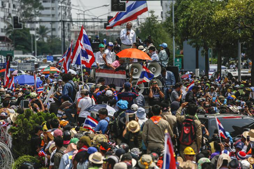 """Chiếc xe chở thủ lĩnh biểu tìnhSuthep Thaugsuban dẫn đầu đoàn xe, với hàng nghìn người ủng hộmỗi nơi ông đi qua.""""No matter where Yingluck is, we will follow,"""" he said."""
