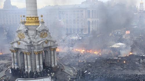Toàn cảnh Quảng trường Độc lập ở thủ đô Kiev. Nơi đây đang bị chia cắt bởi những hàng rào bằng lốp xe. gạch đá, gỗ vụn. Tòa nhà Trade Union, từng bị người biểu tình chiếm làm sở chỉ huy, bị châm lửa đốt hồi đầu tuần và chỉ còn lại những bức tường. Ảnh: RT.