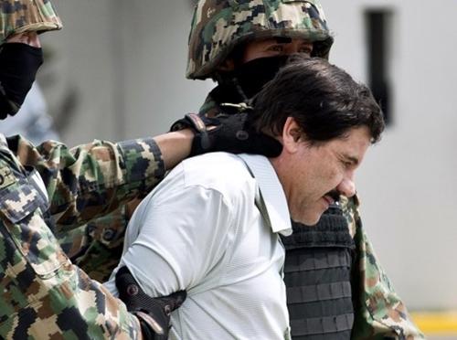 Hai lính thủy quân lục chiến áp giải trùm ma túy Guzman. Ảnh: AFP.