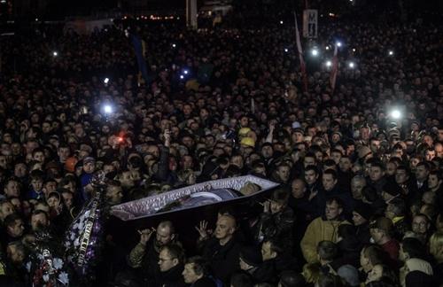 Người dân hôm qua khiêng quan tài của những người thiệt mạng trong các vụ đụng độ với cảnh sát ở Kiev. Ảnh: AFP