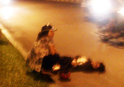 Cô gái nằm bất tỉnh giữa đường sau khi bị cướp xe. Ảnh: Châu Thành