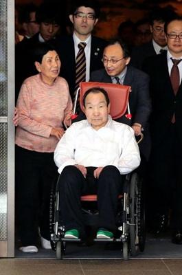 Iwao Hakamada leaves a hotel in Tokyo with his sister, Hideko, to his left, on March 28. (Kazuhiro Nagashima)