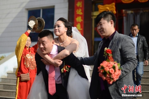 Xu Xiaofei, the groom, carries Dang Shiying on his back to step out of the social welfare house in Taiyuan, north Chinas Shanxi province on March 26, 2014. (CNS/ Wei Liang)