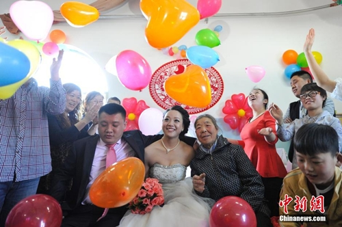 Dang Shiying, her groom and her foster mother take photos at the social welfare house in Taiyuan, north Chinas Shanxi province on March 26, 2014. (CNS/ Wei Liang)