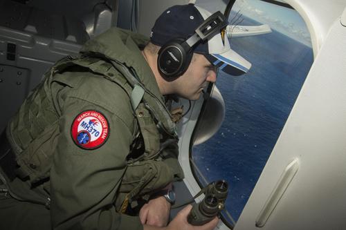 Binh sĩ Mỹ tìm kiếm mảnh vỡ MH370 trên mặt biển từ máy bay Poseidon P8. Ảnh: Reuters.
