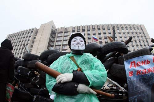 [Caption]A pro-Russian activist wearing a Guy Fawkes mask and holding a bat guards a barricade outside the regional government building in the eastern Ukrainian city of Donetsk on April 13, 2014.Cũng trong ngày hôm nay, một nhóm khoảng 40 người mang theo gậy gỗ cố gắng giành quyền kiểm soát văn phòng công tố tại thành phố Donetsk nhưng bất thành và buộc phải chấp nhận đàm phán.Các tòa nhà chính phủ ở hai thành phố nói tiếng Nga làDonetskvà Luhansk đã bị những người theo chủ nghĩa ly khai chiếm đóng từ tuần trước. Theo giới lãnh đạo thân châu Âu tại Kiev, đây là một phần trong kế hoạch chia rẽ Ukraine của Nga, tương tự như Nga từng áp dụng để sáp nhập Crimea. Theo đó, việc chiếm đóng các tòa nhà chính phủ và căn cứ quân sự được tiến hành nhằm tổ chức một cuộc trưng cầu dân ý.