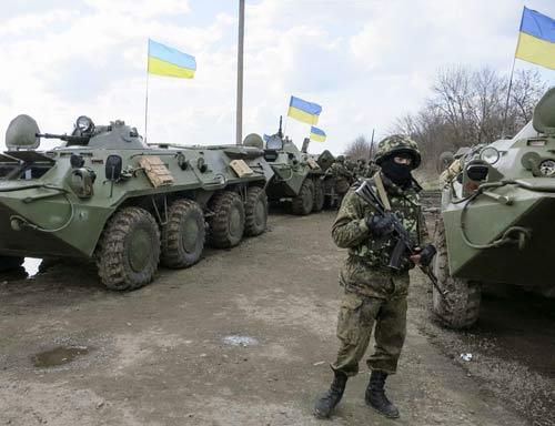 Binh sĩ Ukraine đứng cạnh các xe bọc thép ở một chốt kiểm tra gần thị trấnIzium, phía đông Ukraine. Ảnh: Reuters