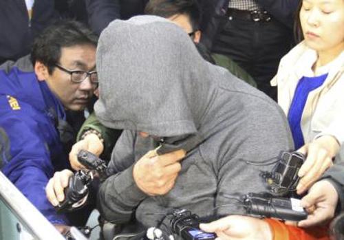 Thuyền trưởng phà Sewol (mặc áo màu xám) trùm kín mặt trong vòng vây báo giới ở thành phố Mokpo. Ảnh: Yonhap