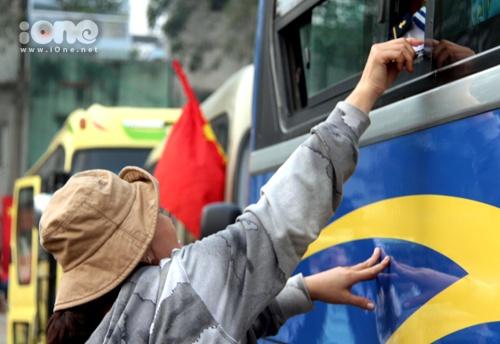 Một bà mẹ tranh thủ nhét vội tờ giấy ghi những điều dặn dò vào tay con trai trước giờ xe lăn bánh rời Sài Gòn.