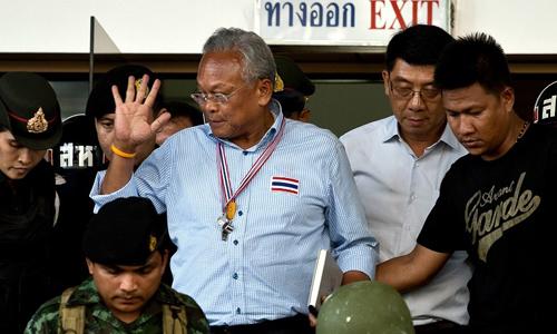 Thủ lĩnh biểu tình Suthep Thaugsuban rời Tòa án Hình sự sau khi nộp tiền bảo lãnh. Ảnh: AFP.
