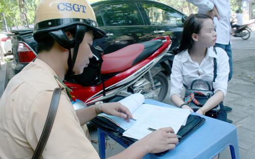 Sáng nay, nhiều người đi xe máy điện, đạp điện bị lập biên bản xử phạt lỗi vượt đèn đỏ, không đội mũ bảo hiểm theo nghị định 171 của Chính phủ. Ảnh: Bá Đô