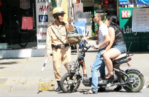 Nhiều người tham gia giao thông bằng xe máy, xe đạp điện vi phạm không đội mũ bảo hiểm. Và phần lớn các xe máy điện chưa được đăng ký biển số.Ảnh: Bá Đô
