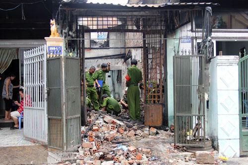 Cảnh sát khám nghiệm hiện trường căn nhà bị cháy rụi. Ảnh: An Nhơn