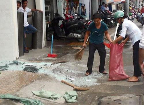 Người của tòa nhà thu dọn mảnh kính vỡ vụn dưới đường. Ảnh: An Nhơn