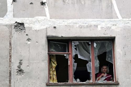 Một người dân quan sát tình hình bên ngoài qua khung cửa kính vỡ nát. Ảnh: RIA Novosti.
