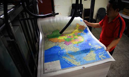 Bản đồ phi pháp mới được in tạiCông nhân kiểm tra tấm bản đồ mới của Trung Quốc tại xưởng in. Ảnh: Reuters.