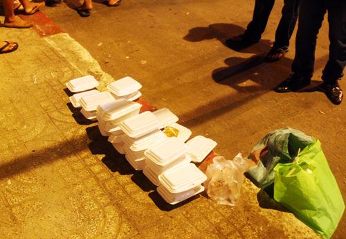 Những hộp cơm từ thiện của nạn nhân còn lại ở hiện trường. Ảnh: An Nhơn