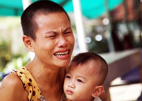 Vợ anh Phước bế con nhỏ khóc ngất trước cái chết tức tưởi của chồng. Ảnh: An Nhơn