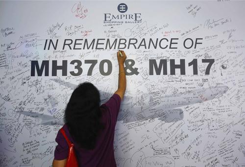 Một người phụ nữ viết lên bảng tưởng niệm các nạn nhân trên hai chuyến bay của Malaysia MH370 và MH17 ởSubang Jaya, ngoại ôKuala Lumpur. Ảnh: Reuters